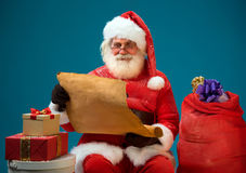 Good Santa Claus holding vintage roll and reads a long listof gifts for children Stock Image