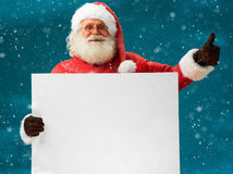 Good Santa Claus holding white blank banner or copy space for your text. / Merry Christmas & New Year's Eve concept / Closeup on blurred blue background stock photo