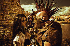 The good slave, the bad and the ugly. Raider with mohawk hairstyle, young pretty slave  in iron mask and slave trader posing over post-apocalyptic wasteland Royalty Free Stock Photography