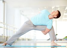 Good stretching. Portrait of young man doing stretching exercise in gym Royalty Free Stock Photos