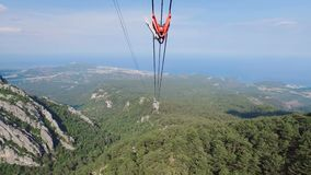 Good sunny weather on top of high mountain in Turkey, camera moves along cableway. Forest, rocks and seacoast are below stock video footage
