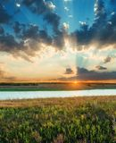 sunset in low clouds over river and green meadow Royalty Free Stock Photo