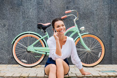 Good talk with friend. Attractive young smiling woman talking on the mobile phone while sitting at the roadside near her vintage bicycle Royalty Free Stock Photography