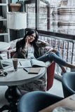 Good talk with friend. Attractive young smiling woman talking on smart phone and looking away while sitting in restaurant near the window Stock Photography