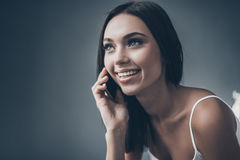 Good talk with friend. Attractive young woman talking on hte mobile phone and smiling while sitting against grey wall Stock Photo