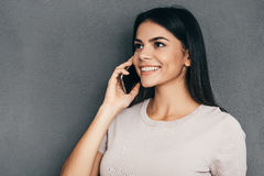 Good talk with friend. Attractive young woman talking on the mobile phone and smiling while standing against grey background Stock Images