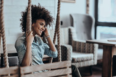 Good talk with friend. Beautiful young African woman talking on smart phone and smiling while sitting on the swing Stock Photo