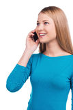 Good talk with friend. Beautiful young woman talking on the mobile phone and smiling while standing against white background Stock Image