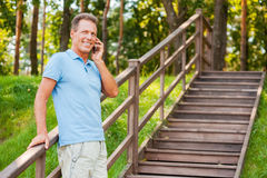 Good talk with friend. Cheerful mature man talking on the mobile phone and smiling while standing at wooden staircase Stock Photos