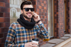 Good talk with friend. Cheerful young man holding coffee cup and talking on the mobile phone while standing at the street Stock Photos