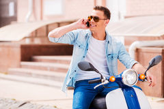 Good talk with friend. Cheerful young man sitting on scooter and talking on the mobile phone Stock Photography