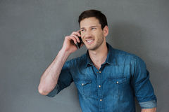 Good talk with friend. Cheerful young man talking on the mobile phone and smiling while standing against grey background Royalty Free Stock Photo