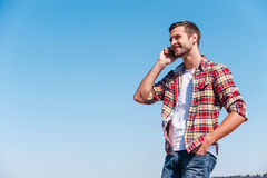 Good talk with friend. Cheerful young man talking on mobile phone and smiling while standing outdoors with blue sky as background Royalty Free Stock Photos