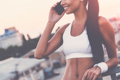 Good talk with friend. Close-up of beautiful young woman in sports clothing talking on the mobile phone and smiling while standing on the bridge with evening Stock Photos