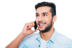 Good talk with friend. Handsome young Indian man talking on the mobile phone and smiling while standing against white background Stock Photography
