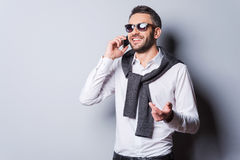 Good talk with friend. Handsome young man in smart casual wear and sunglasses talking on the mobile phone and smiling while standing against grey background Royalty Free Stock Photography