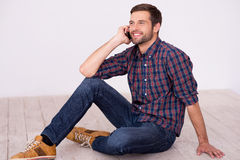Good talk with friend. Handsome young man talking on the mobile phone and smiling at camera while sitting on hardwood floor Royalty Free Stock Photography