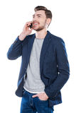 Good talk with friend. Handsome young man talking on the mobile phone and smiling while standing against white background Royalty Free Stock Photography