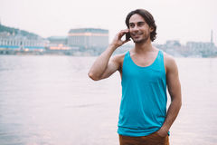 Good talk with friend. Handsome young man in talking on the mobile phone and smiling while standing at the riverside Royalty Free Stock Photos