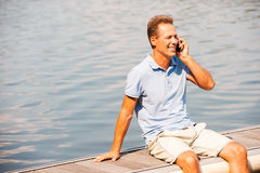 Good talk with friend. Happy mature man talking on the mobile phone and smiling while sitting at the quayside Stock Photos