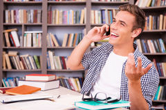 Good talk with friend. Happy young man talking on the mobile phone and gesturing  while sitting at the desk in library Royalty Free Stock Image