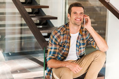 Good talk with friend. Happy young man talking on the mobile phone while sitting on staircase in his house Stock Photography