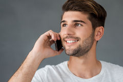 Good talk with friend. Happy young man talking on mobile phone and smiling while standing against grey background Stock Image