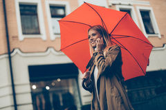 Good talk with friend. Low angle view of attractive young smiling woman carrying umbrella and talking on the mobile phone while walking down the street Royalty Free Stock Images