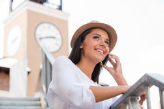 Good talk with friend. Low angle view of beautiful young woman in funky hat looking away and smiling while standing outdoors Royalty Free Stock Image