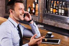 Good talk with friend. Side view of happy young man in shirt and tie talking on the mobile phone and gesturing while sitting at the bar counter Royalty Free Stock Images