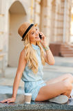Good talk with friend. Side view of young woman talking on the mobile phone and smiling while sitting outdoors Royalty Free Stock Image