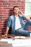 Good talk. Handsome young man sitting on the floor and talking on the mobile phone while digital tablet and documents laying near him Royalty Free Stock Image