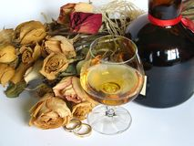 Good Taste. A set of diamond-rings, right next to a glass of brandy, a bottle, and a bouquet stock photos