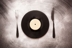 Good taste in music. Vinyl record in the form of plates on the silhouette fork and knife Stock Photos