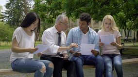 Good teacher giving additional tasks to multiracial students in university park. Stock photo royalty free stock images