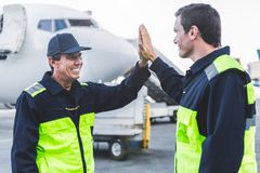 Happy engineers clapping arms at airdrome Stock Image