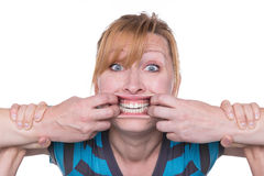 Good teeth. Woman defends herself against two hands opening her mouth Stock Images