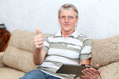 It is a good thing a tablet PC for active senior man Royalty Free Stock Photography