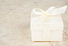 Good Things Come in Small Packages. Small gift box and bow against variegated beige background Royalty Free Stock Photos