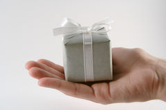 Good things come in small packages. A small gift box held in a hand Royalty Free Stock Photography