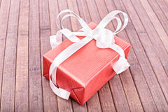 Good things come in small packages. Close-up shot of a small gift box on a wooden background Royalty Free Stock Photo
