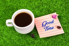 Good time with coffee. Good time word in memo with coffee cup , coffee bean and dried rose bud on grass royalty free stock image