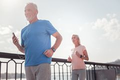 Confident athletic man smiling and running. Good time. Confident athletic aged men listening to music smiling and running across the quay Stock Images