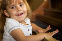 A good time playing the piano. A little girl having fun playing the piano Stock Photography