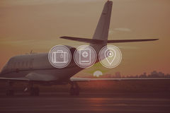 Good time for travelling. Digitally composed icon set over a picture of private jet landing in sunset Stock Photo