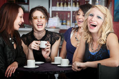 Good Times. Pretty young blonde laughing with three friends in a cafe stock photography
