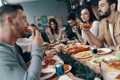Good times with friends. Group of young people in casual wear eating pizza and smiling while having a dinner party indoors royalty free stock photography