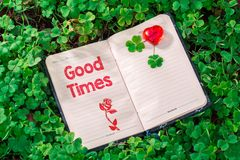 Good times text in notebook. On Clovers with red heart in the garden stock photography