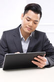 A good trader, the secret of success. Handsome man in business suit sitting at his desk in his office stock photography