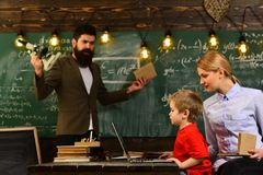 Good tutors are often communication masters, Old books on a round wooden table, Attentive teacher talking to her student. In science class at the university Stock Photo